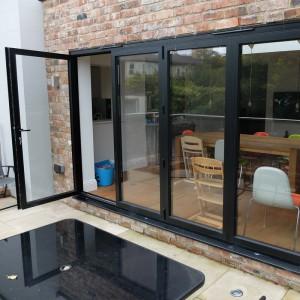Aluminium bi-fold doors with through door open