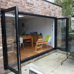 Black bi-folding doors opening on to the patio
