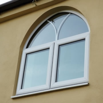 Arched white French window with decorative astragal bars