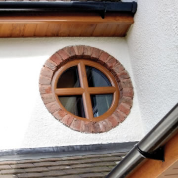 Small woodgrain circular window with cross astragal bar