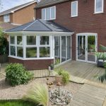 White tiled roof conservatory with black tiled roof.